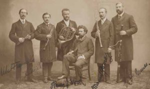 Figure 1. Sir Henry Wood and the soloists of the Promenade Concerts. Flute: Albert Fransella, oboe: Desiré Lalande, French horn: Emil Borsdorf, clarinet: Manuel Gómez and bassoon: Edwin James. William Whiteley Ltd, c. 1899. © National Portrait Gallery, London.